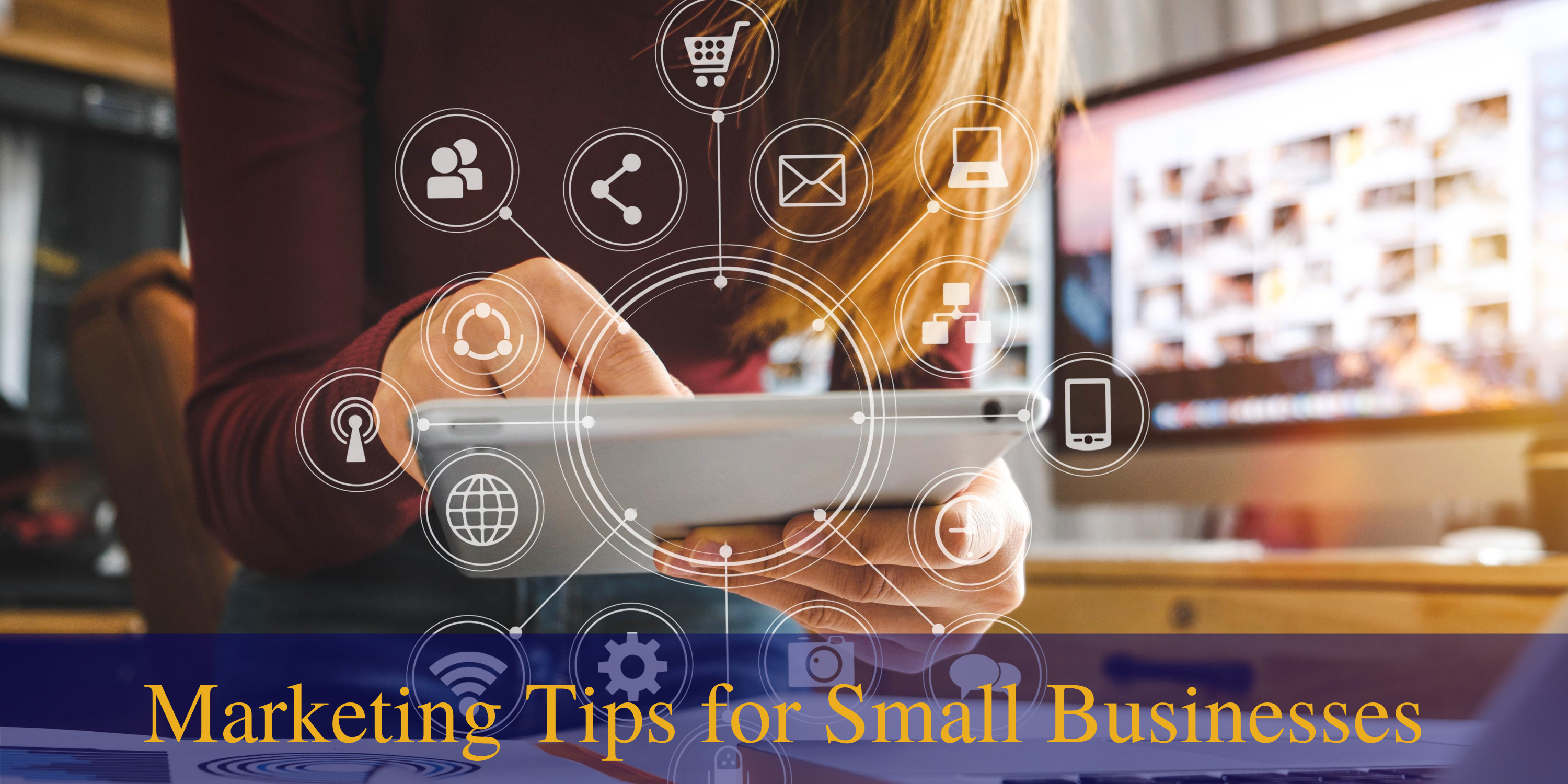 Woman using mobile device with desktop computer in the background to improve marketing with small businesses.