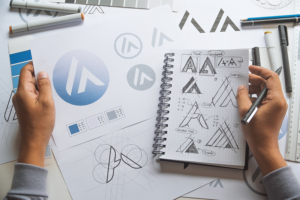 Brand refresh of a logo, with multiple sketches of logos on paper and in a notebook.