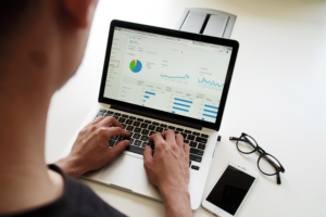 A white man looking at website analytics on his computer - not one of the mistakes small business make.